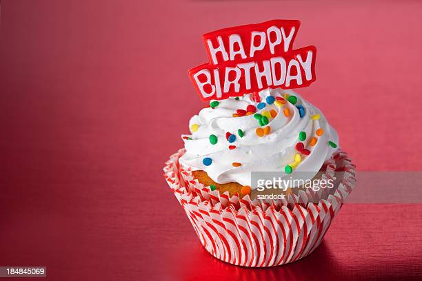 Birthday cupcake with colored sprinkles in a red background