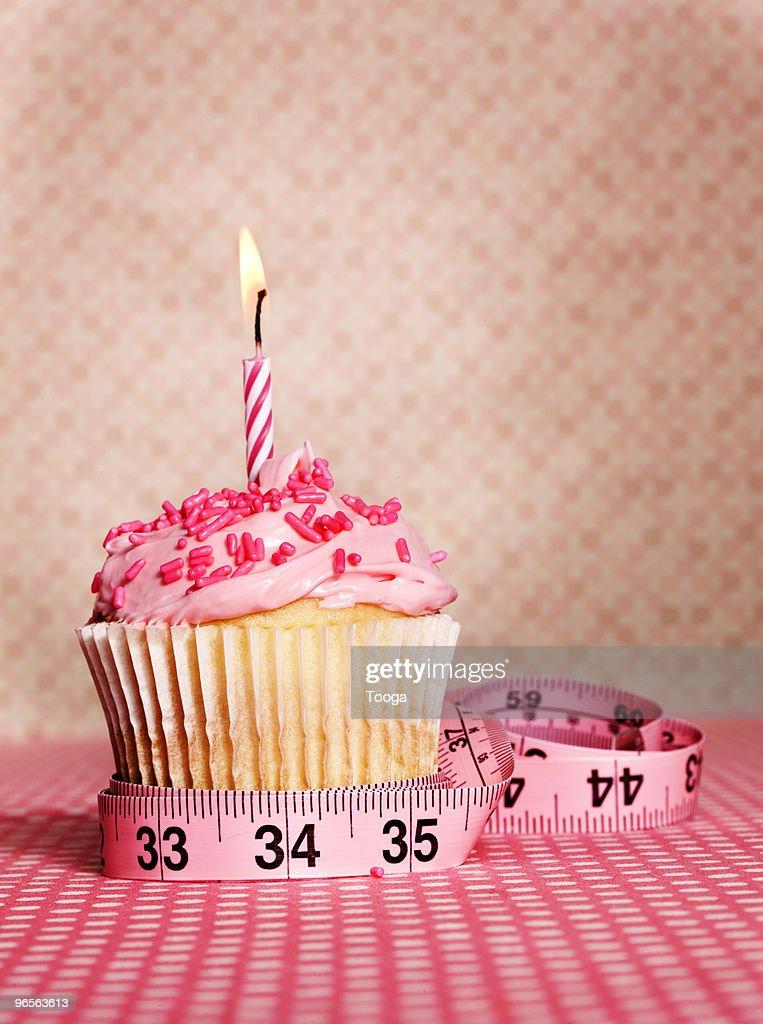 Birthday cupcake with measuring tape : Stock Photo