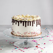 Birthday Drip Layered Cake with chocolate ganache and sprinkles on a white background with party decor. Horizontal. Copy space. Celebration concept. Trendy Drip Cake.