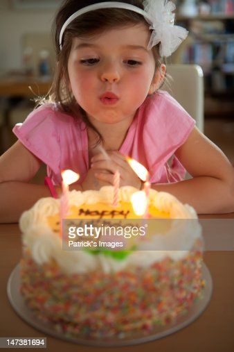 Birthday girl blowing candles : Stock Photo