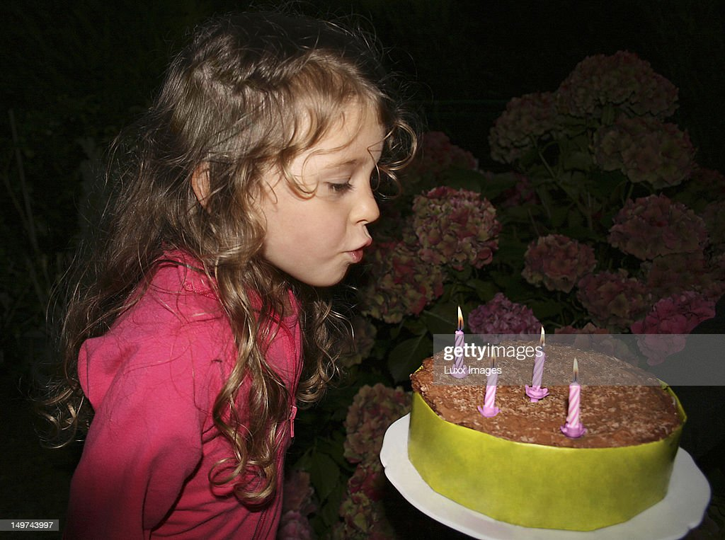 Birthday girl blowing out candles on a cake : Stock Photo