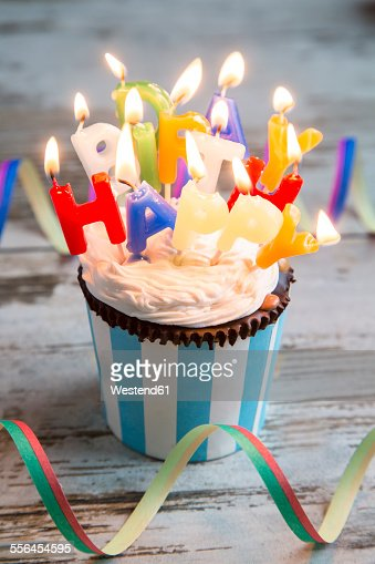 Birthday muffin with chocolate buttons and lighted candles