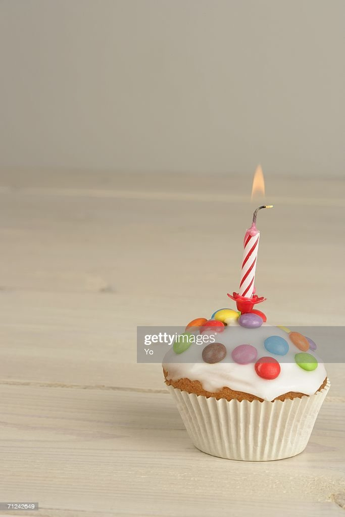 Birthday muffin with icing, sprinkles and candle : Stock Photo
