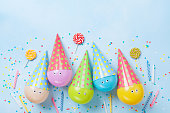 Birthday or party background. Funny balloons, candy and confetti on blue table top view. Flat lay. Invitation card.