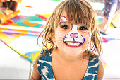 Happy little girl with her face painted grins at the camera