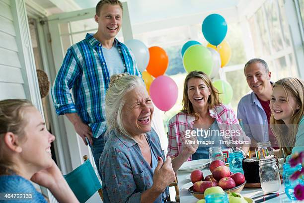 A birthday party in a farmhouse kitchen. A group of adults and children gathered around a chocolate cake.