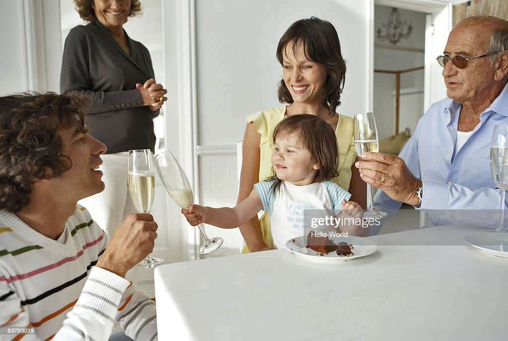 birthday toddler toasting milk glass with father : Stock Photo