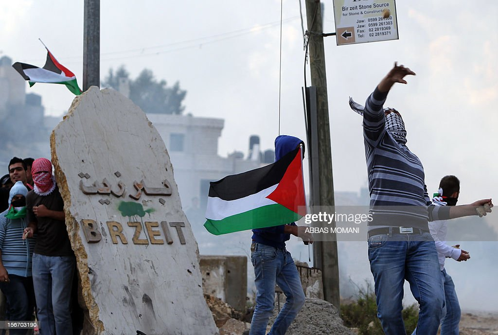 A Birzeit University student throws a stone as others take cover behind the university's sign during clashes with Israeli soldiers at the Atara checkpoint close to the university as they protest against Israel's military action on the Gaza Strip, on November 19, 2012. Israeli air strikes across the Gaza Strip killed 13 people, raising the Palestinian death toll to 90 as Israel's relentless air campaign entered its sixth day.