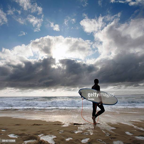 surfer holding his surfboard in front of the ocean
