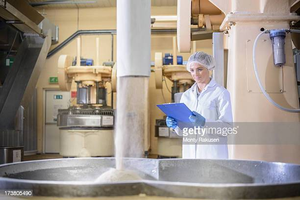 Biscuit factory worker inspecting bulk amounts of ingredients