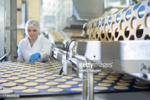 Biscuit factory worker inspecting freshly made biscuits on production line