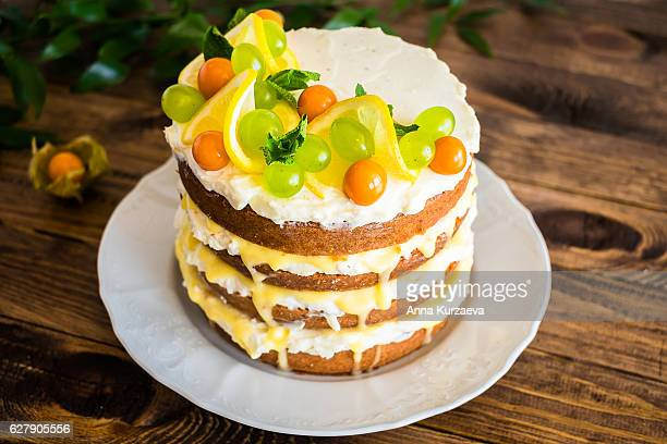 Biscuit layered cake with cream cheese and lemon curd decorated with fresh mint leaves, physalis, lemon slices and green grapes on a plate