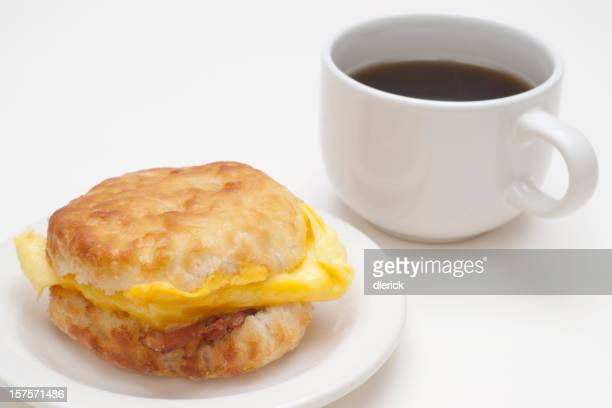 biscuit with bacon, cheese,  eggs and coffee