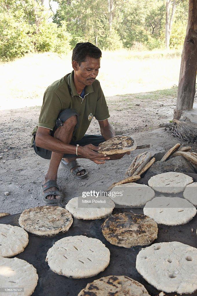 Bishnoi man making roti (bread) in traditional way, Rajasthan, India : Stock Photo