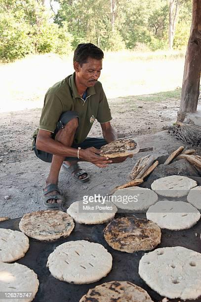 Bishnoi man making roti (bread) in traditional way, Rajasthan, India