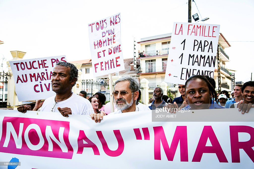 Bishop Emmanuel Lafont (C) stands behind a banner as he takes part in a protest against same-sex marriage, in Cayenne, in French Guiana, on January 12, 2013. Tens of thousands are set to march in Paris, on January 13, 2013 to denounce government plans to legalise same-sex marriage and adoption which have angered many Catholics and Muslims, France's two main faiths. The French parliament is to debate the bill -- one of the key electoral pledges of Socialist President at the end of this month.