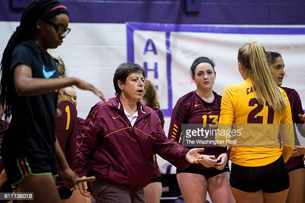 Bishop Ireton head coach Kathy Guttmann gathers her team for a time out during their match against Bishop Ireton on Wednesday September 28 2016 in...