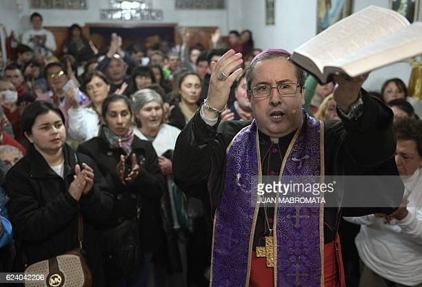 Bishop Manuel Acuna holds the Holy Bible during a ritual at the 'El Buen Pastor' parish in Santos Lugares outskirts of Buenos Aires on September 6...