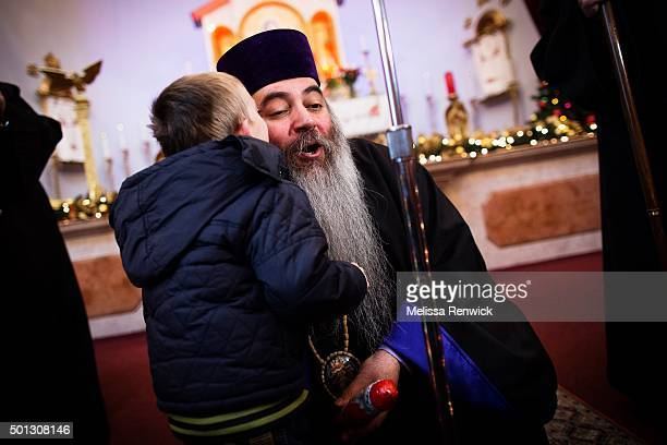 TORONTO ON DECEMBER 11 Bishop Meghrig Parikian gets a kiss from a Syrian refugee after handing him a chocolate Santa Claus during a welcome mass at...