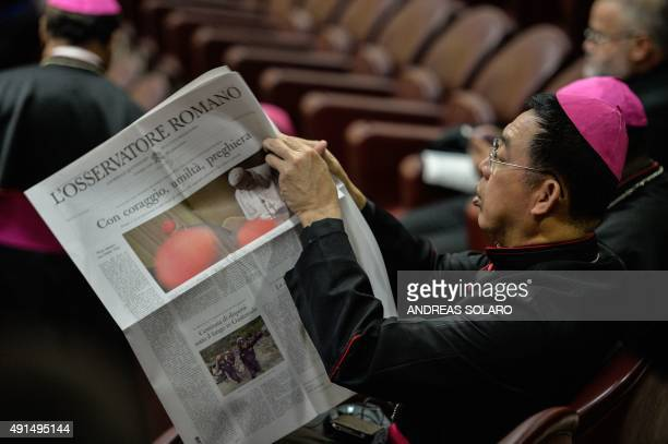 A bishop reads the Osservatore Romano before the arrival of Pope Francis for the second morning session of the Synod on the Family at the Vatican on...