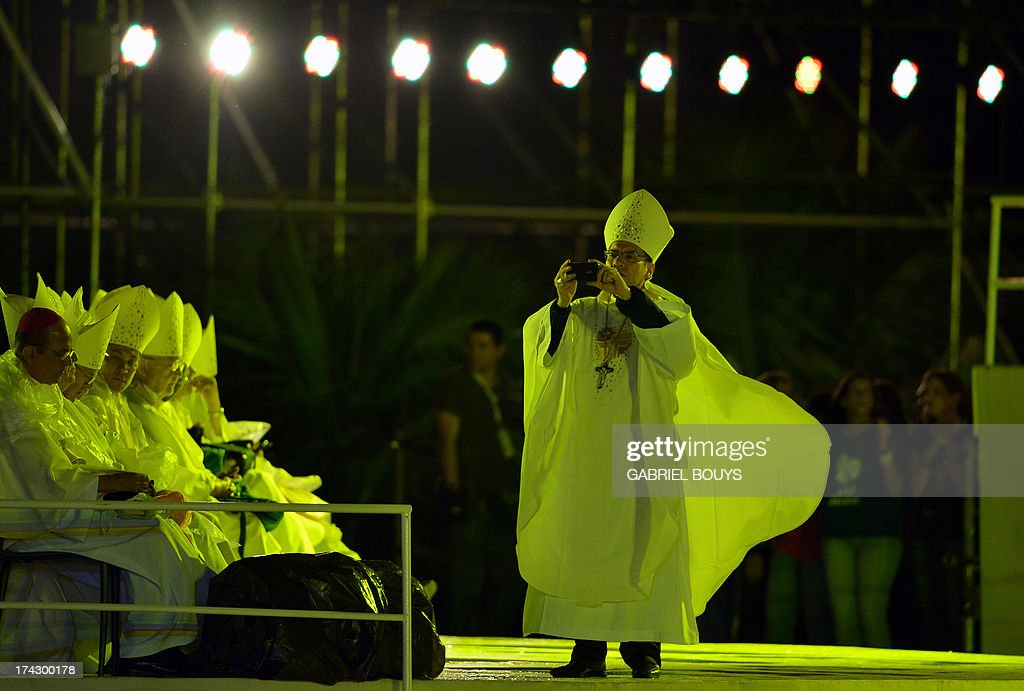 A bishop takes pictures before the start of the World Youth Day (WYD) opening mass, at Copacabana beach in Rio de Janeiro, Brazil, on July 23, 2013. The highlight of the landmark visit of Pope Francis to the world's most populous mainly Catholic country will be WYD, a five-day event that kicks off today. Pope Francis's popularity on his Latin American home turf posed a challenge to Brazilian authorities Tuesday after adoring crowds mobbed his car on his arrival on Monday. AFP PHOTO / GABRIEL BOUYS
