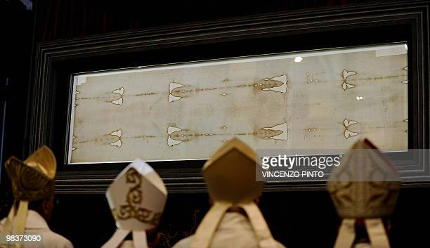Bishops pray in front of the Shroud of Turin at the end of a mass celebrated by Turin Cardinal Severino Poletto to mark the first day of the display...