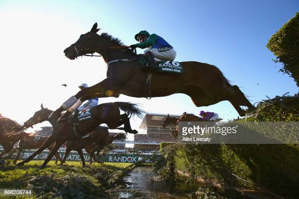 Bishops Road ridden by Jamie Moore clears the Water Jump on during the 2017 Randox Health Grand National at Aintree Racecourse on April 8 2017 in...