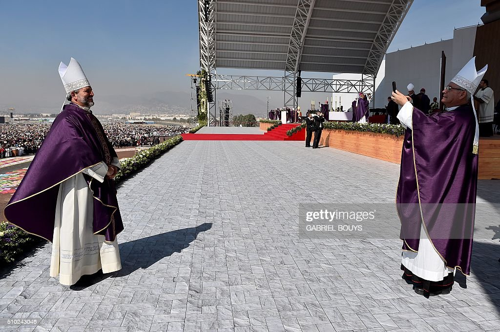 Bishops take pictures before Pope Francis celebrates an open-air mass in Ecatepec --a rough, crime-plagued Mexico City suburb-- on February 14, 2016. Pope Francis has chosen to visit some of Mexico's most troubled regions during his five-day trip to the world's second most populous Catholic country. AFP PHOTO/GABRIEL BOUYS / AFP / GABRIEL BOUYS