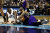 Bismack Biyombo of the Charlotte Bobcats and Michael Beasley of the Phoenix Suns battle for a loose ball during their game at Time Warner Cable Arena...