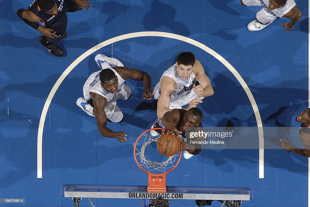 Bismack Biyombo #0 of the Charlotte Bobcats dunks against Andrew Nicholson #44 and Nikola Vucevic #9 of the Orlando Magic on January 18, 2013 at Amway Center in Orlando, Florida.