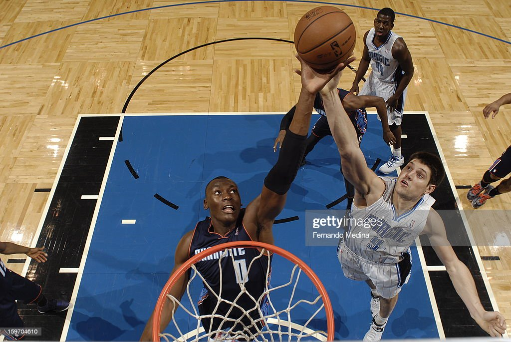 Bismack Biyombo #0 of the Charlotte Bobcats goes up for a rebound against Nikola Vucevic #9 of the Orlando Magic on January 18, 2013 at Amway Center in Orlando, Florida.