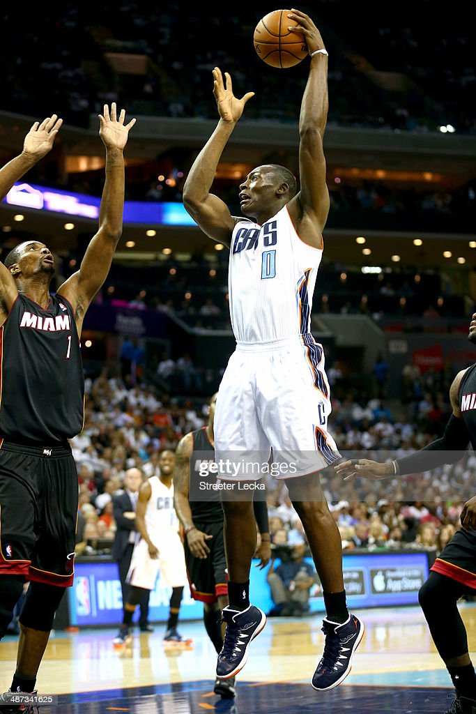Bismack Biyombo #0 of the Charlotte Bobcats shoots over Chris Bosh #1 of the Miami Heat in Game Four of the Eastern Conference Quarterfinals during the 2014 NBA Playoffs at Time Warner Cable Arena on April 28, 2014 in Charlotte, North Carolina.