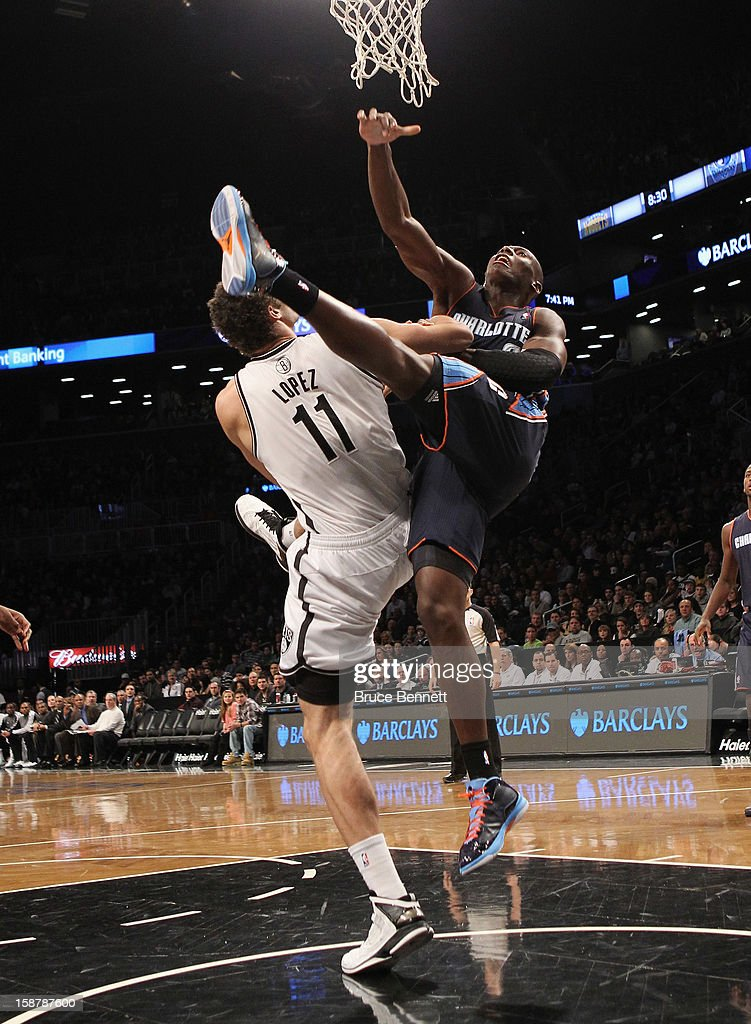 Bismack Biyombo of the Charlotte Bobcats takes the offensive foul against Brook Lopez of the Brooklyn Nets in the first quarter at the Barclays...