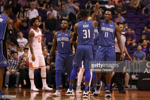 Bismack Biyombo of the Orlando Magic high fives Terrence Ross after scoring against the Phoenix Suns during the second half of the NBA game at...