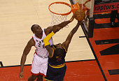 Bismack Biyombo of the Toronto Raptors blocks a shot on Kyrie Irving of the Cleveland Cavaliers in Game Three of the Eastern Conference Finals during...