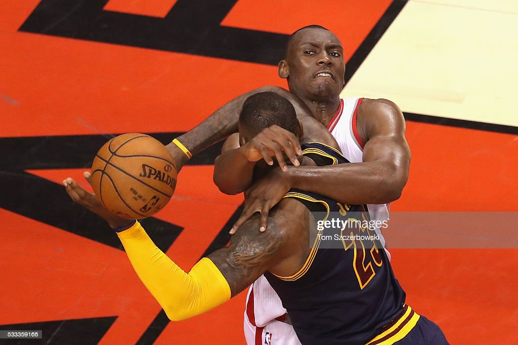 Bismack Biyombo of the Toronto Raptors fouls LeBron James of the Cleveland Cavaliers during the 4th quarter in game three of the Eastern Conference...