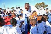 Bismack Biyombo of the Toronto Raptors huddles kids up during the Boys Girls Club of Protea Glen court dedication as part the Basketball Without...