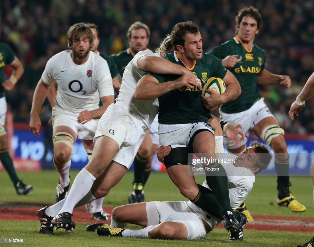 Bismarck du Plessis of South Africa is tackled by Joe Marler and Toby Flood during the second test match between South Africa and England at Ellis...