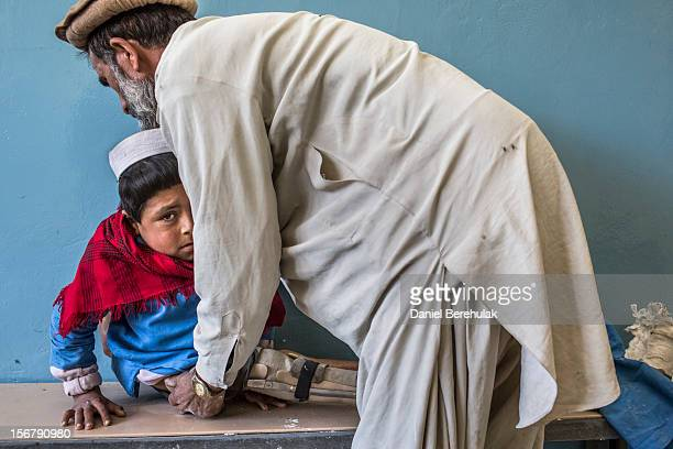 Bismillah Gul suffering from poliomyelitis is helped by his father Masta Gul after having travelled from Khost province to get treatment at the...