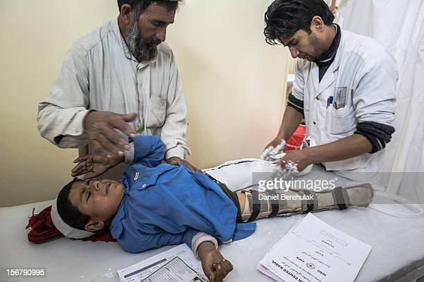 Bismillah Gul suffering from poliomyelitis is helped by his father Mastagul after having travelled from Khost province to get treatment at the...