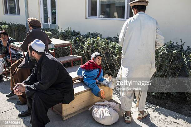 Bismillah Gul suffering from poliomyelitis waits with his father Masta Gul after having travelled from Khost province to get treatment at the...