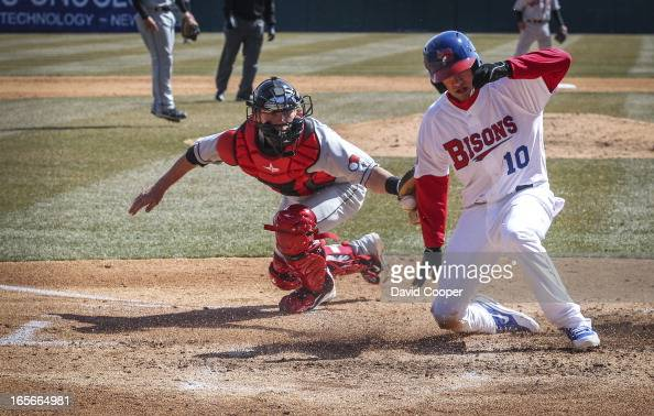 Bisons Ryan Goins slides in safe at home ahead of the tag of Red Wings catcher Chris Herrmann during opening day for the Blue Jays new AAA farm team...