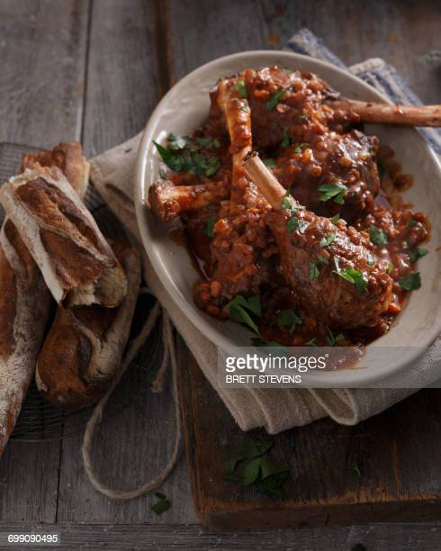 Bistro meal of lamb shanks in red wine on table