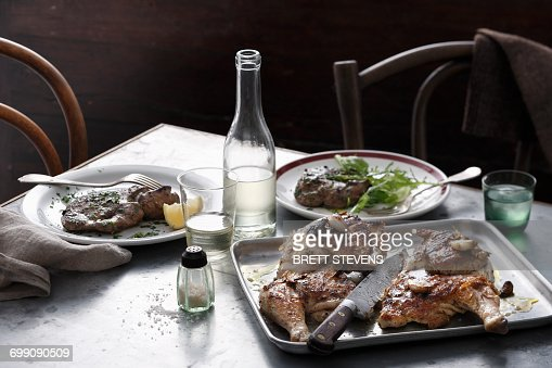 Bistro meal of roast spatchcock and calf liver with white wine on table