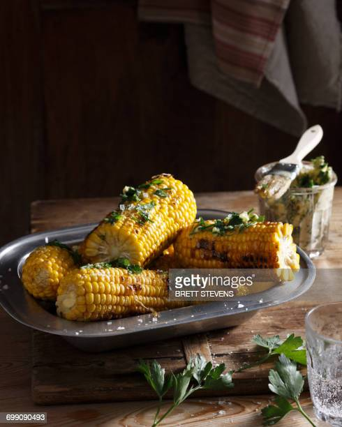 Bistro table with dish of corn on the cob and herb butter