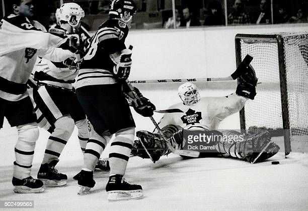 A bit crowded Leaf goalie Rick St Croix sprawls in front of his net as Boston Bruins attacker Tom Fergus tries to get that skipping puck past him The...