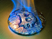Bitcoin metal silver coin is burning with blue flame. It means hot price or value and high exchange rate of crypto currency on market. It is crisis and fall to lose investments due to financial risk t