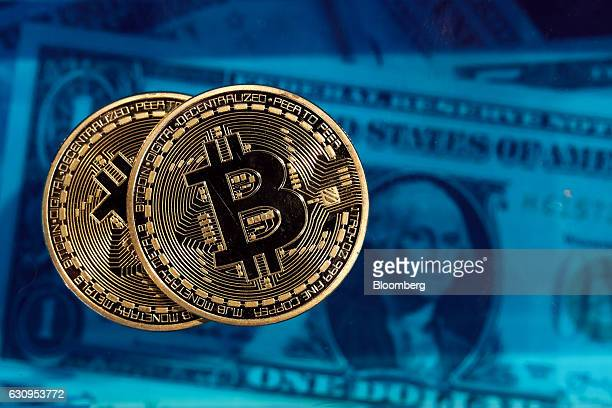 Bitcoin tokens sit next to a collection of US one dollar bills in this arranged photograph in London UK on Wednesday Jan 4 2017 The electronic coin...