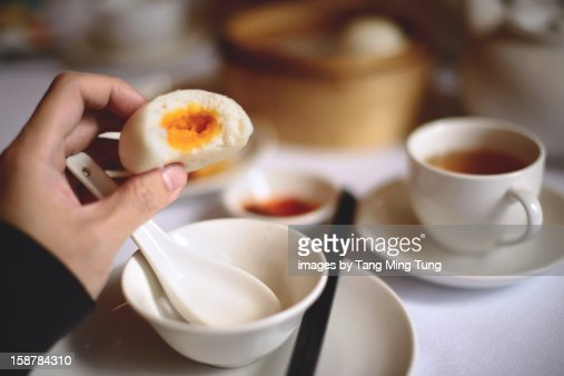 A bite on an egg custard bun : Stock Photo