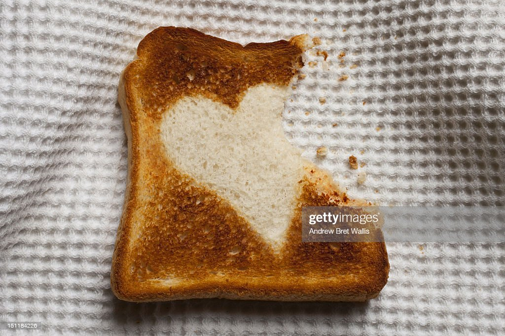 Bite taken out of heart shaped toast on a napkin : Stock Photo